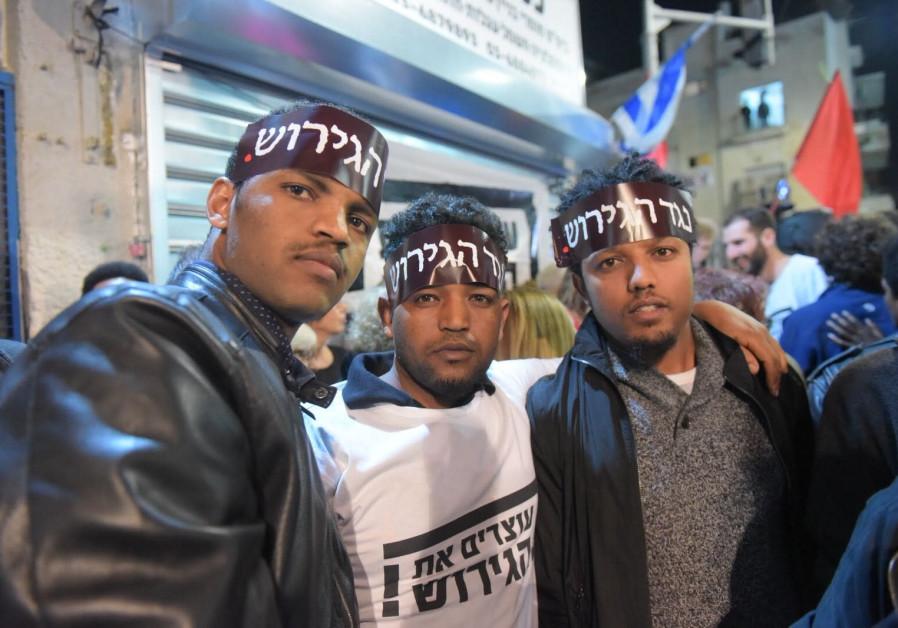 "Three residents of South Tel Aviv attending the anti-deportation protest in Tel Aviv on February 24, 2018. Their headbands read ""against the deportation."" (Courtesy)"