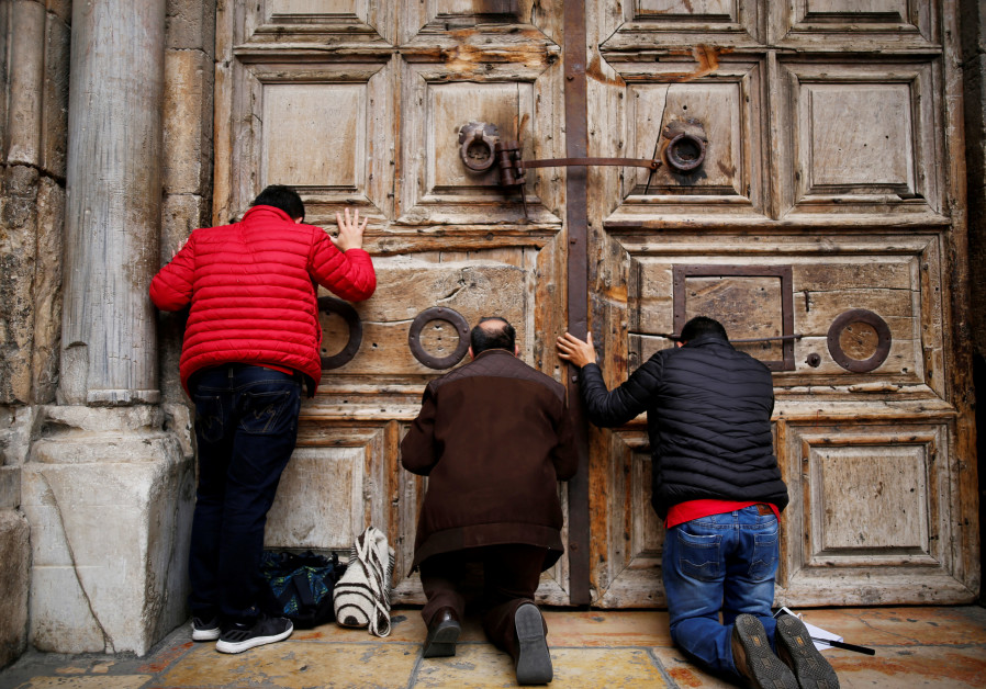 Worshippers kneel and pray in front of the closed doors of the Church of the Holy Sepulchre