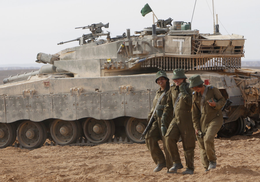 Israeli female soldiers walk in front of a tank at the end of their tank instructors course
