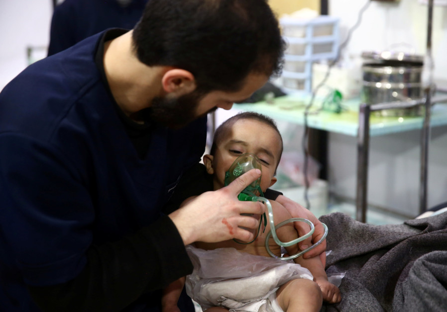 Man with a child in a hospital in the besieged town of Douma, Eastern Ghouta, Damascus, Syria