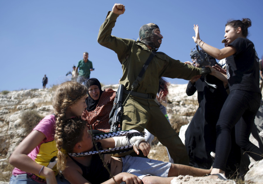 A Palestinian family scuffles with an Israeli soldier in the West Bank