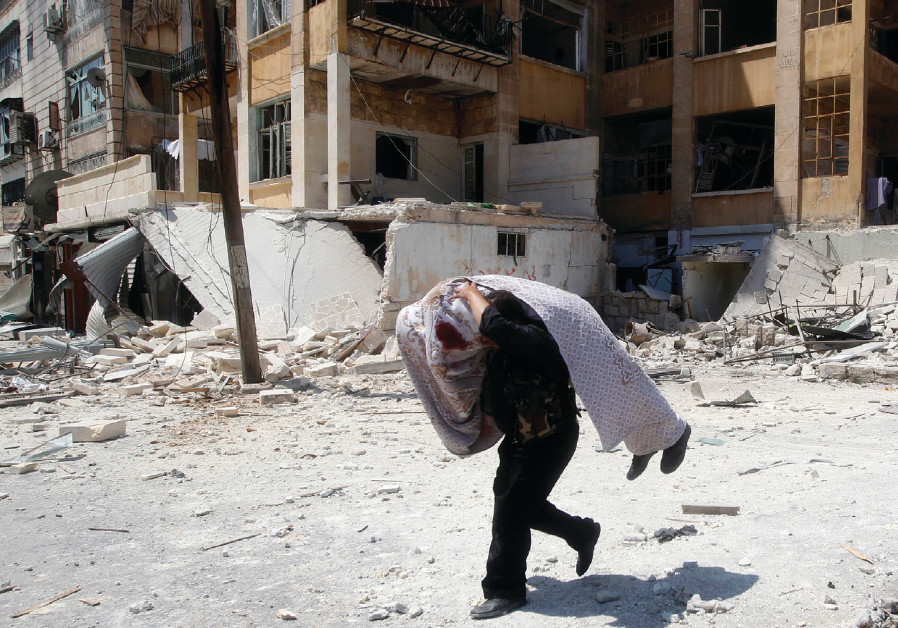 A FREE Syrian Army  ghter carries the body of a fellow  ghter during clashes in Aleppo in August 201