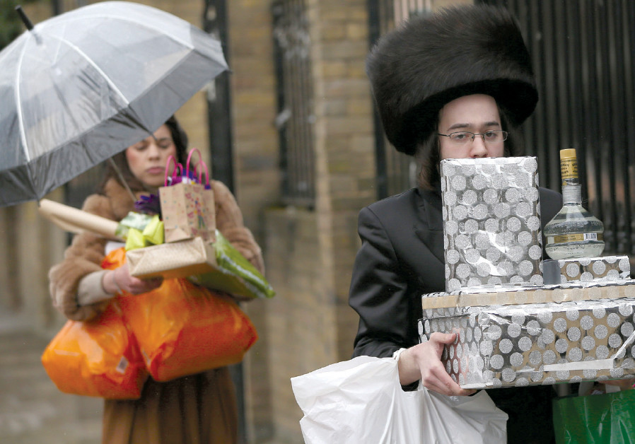 MEMBERS OF the Jewish community carry gifts as they celebrate Purim in London in 2016