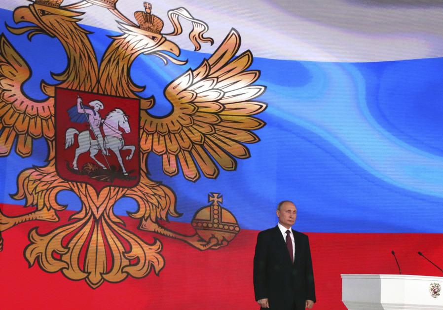 Russian President Vladimir Putin stands on the stage as he addresses the Federal Assembly in Moscow,