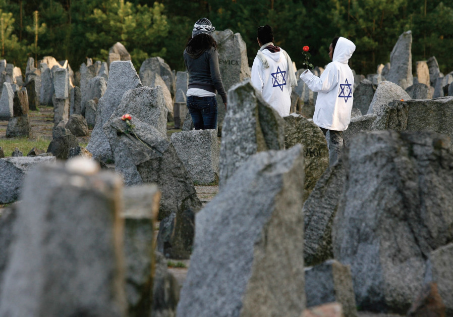 YOUTHS STAND among stones at Treblinka Nazi Death Camp memorial.