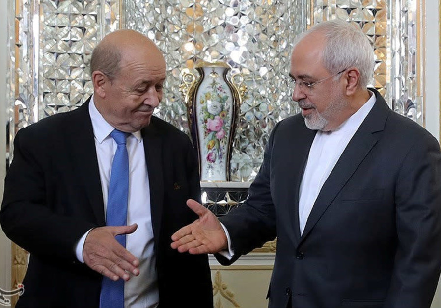 Iranian Foreign Minister Mohammad Javad Zarif reaches out to shake hands with French Foreign Affairs