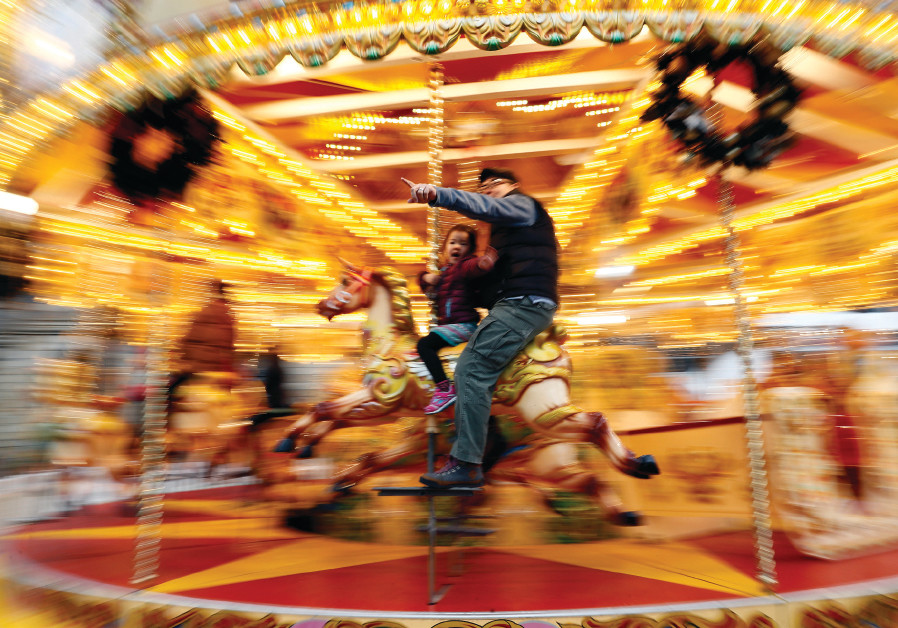 EOPLE RIDE a merry-go-round outside the Natural History Museum in London last year