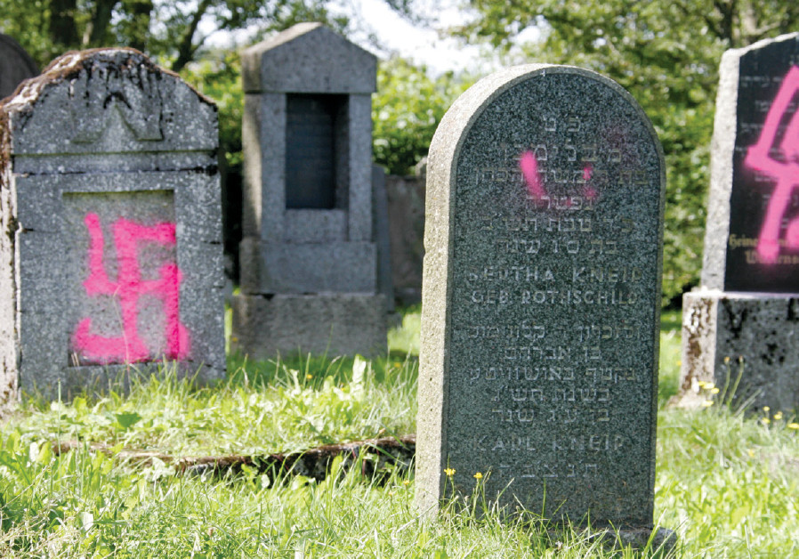 GRAVES DESECRATED by vandals with Nazi swastikas and antisemitic slogans are seen in the Jewish ceme