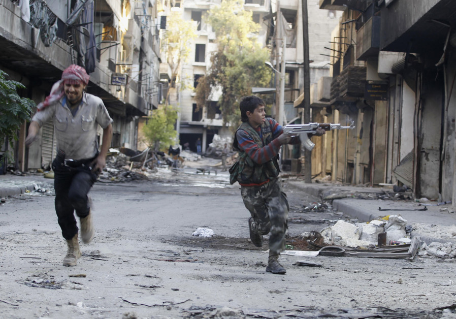 Mohammad (R), a 13 yr-old fighter from the Free Syrian Army, aims his weapon as he runs from sniper