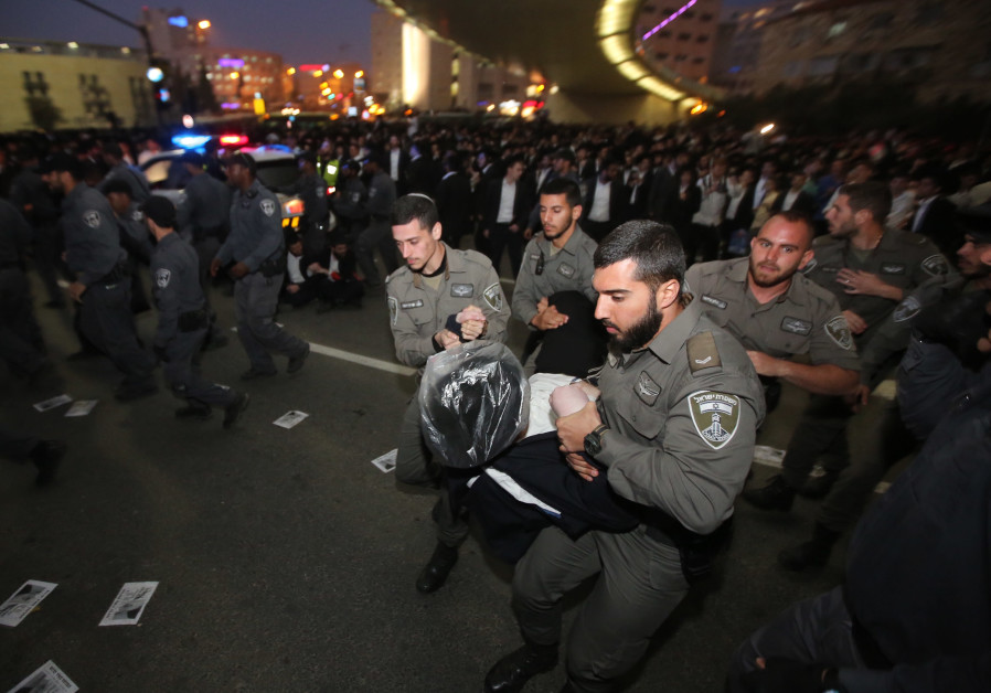 Israel police carry a haredi protestor during an anti-conscription demonstration in Jerusalem, March