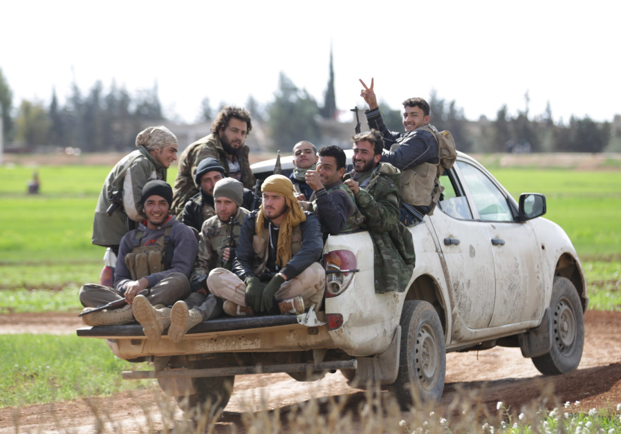 Rebel fighters from 'Jaysh al-Sunna' gesture as they ride a vehicle near Aleppo, Syria