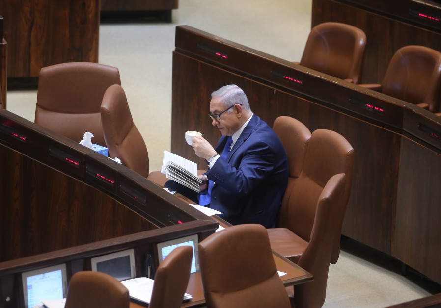 Prime Minister Benjamin Netanyahu reads in the Knesset, March 12, 2018.