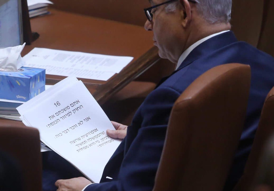 Prime Minister Benjamin Netanyahu reads from his speech in Knesset on March 12, 2018.