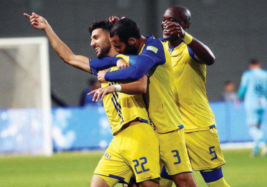 Maccabi Tel Aviv midfielder Avi Rikan (left) celebrates with teammates Yuval Spungin (center)