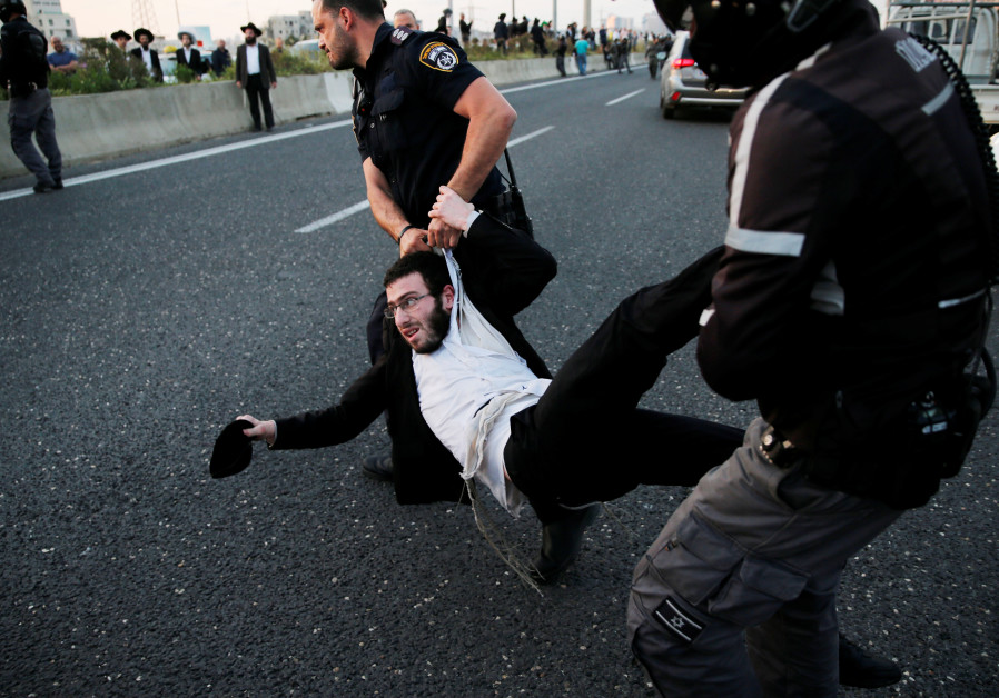 An Israeli ultra-Orthodox Jew is being carried away by police after blocking a road during a protest