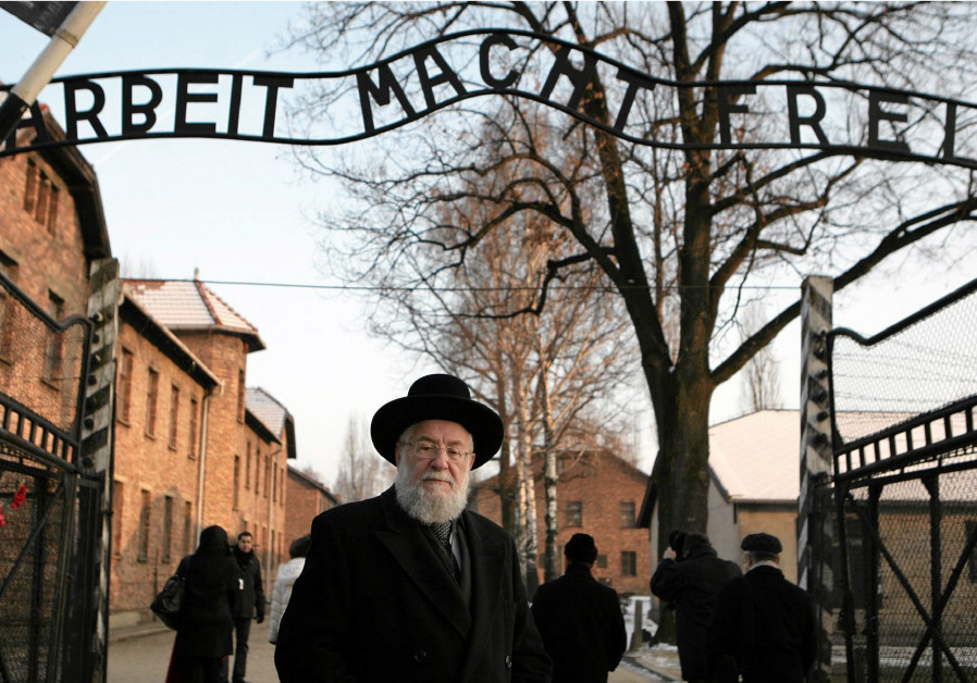 RABBI YISRAEL MEIR LAU stands at the main gate of the former Nazi death camp of Auschwitz with the w