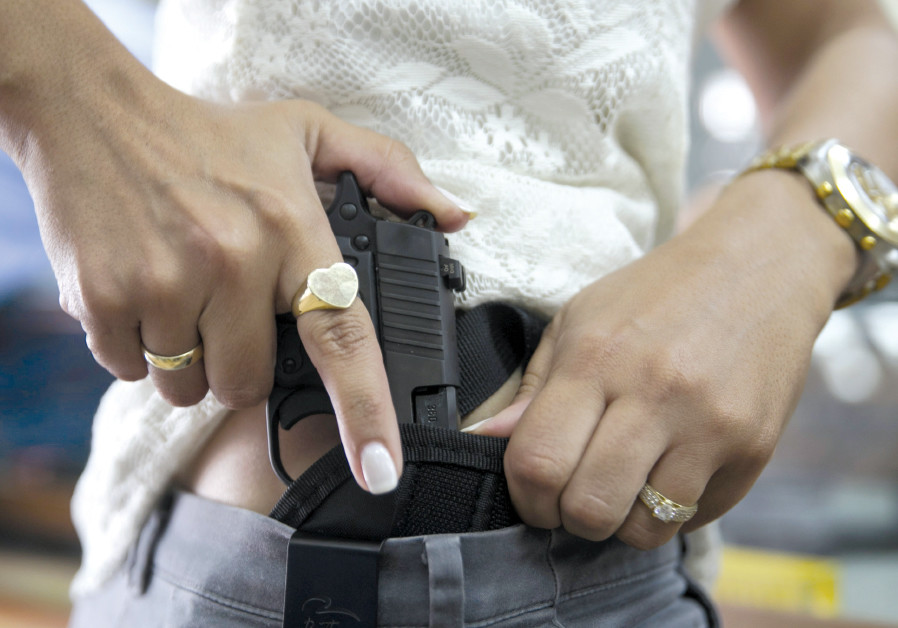 A WOMAN checks out a new pistol at a gun shop in Tel Aviv in 2015