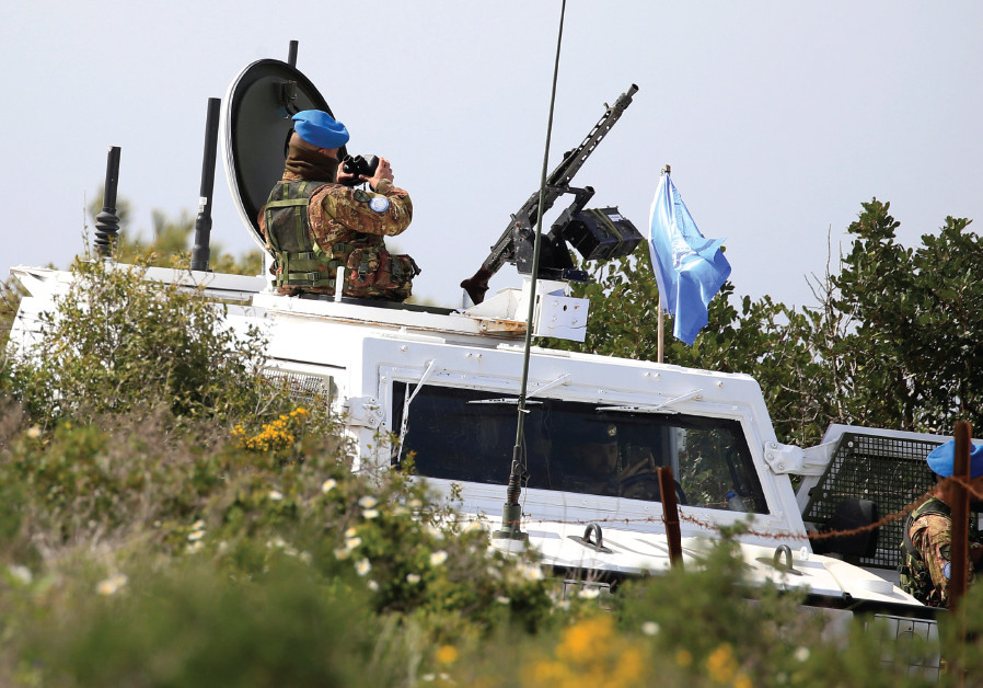 UNITED NATIONS Interim Force in Lebanon (UNIFIL) peacekeepers watch as Israeli workers build a wall
