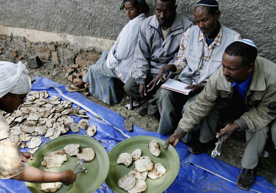 An Ethiopian Jewish woman gives matzahto a man ahead of Passover