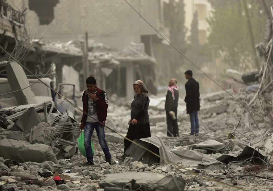 PEOPLE WALK through debris in the center of Afrin, Syria, on March 24, 2018.