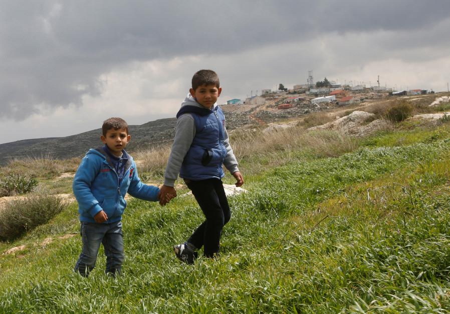 Palestinian boys walk near Jewish settlements in the West Bank village of Jaloud near Nablus
