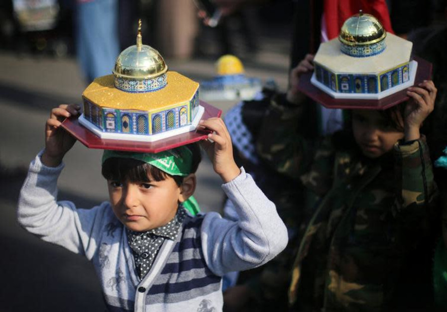 Palestinian children hold models depicting the Dome of the Rock during a protest against U.S. Presid