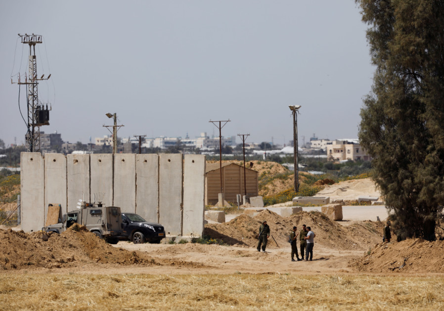 Israeli soldiers stand close to a security barrier near the border between Israel and the Gaza Strip
