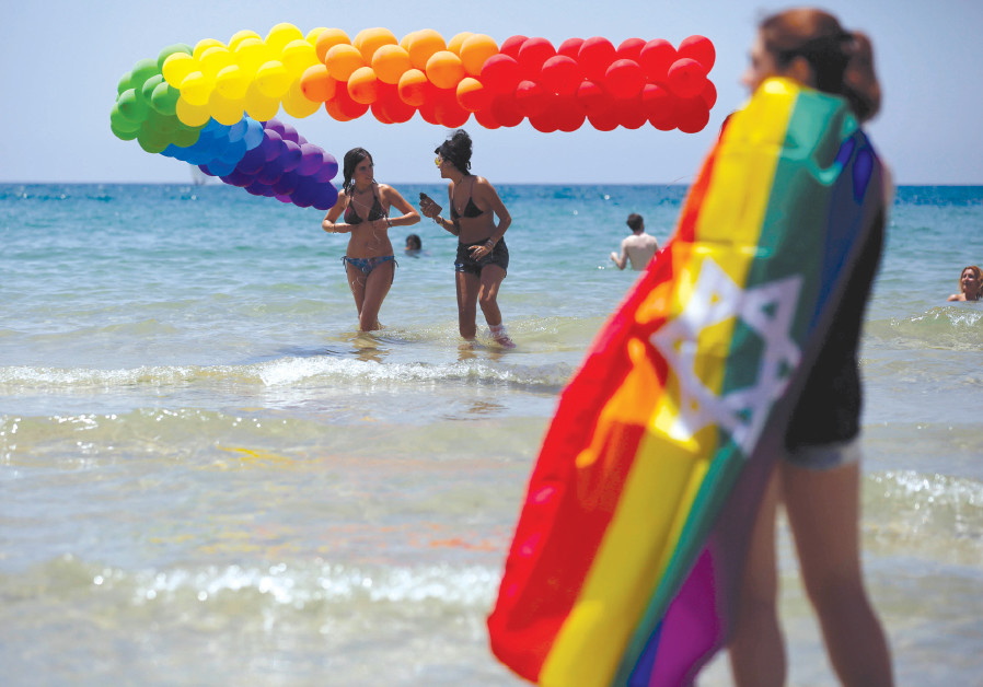 REVELERS DIP in the Mediterranean Sea as they take part in a Gay Pride parade in Tel Aviv last year