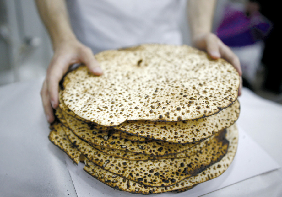 A MAN wraps fresh matza during Passover in Ashdod in 2016