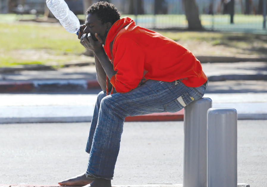 AN AFRICAN migrant sits on the street in Tel Aviv, earlier 2018