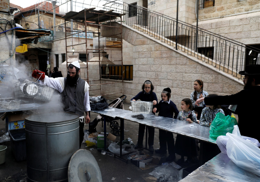 An ultra-Orthodox Jewish man dips cooking utensils in boiling water to remove remains of leaven in p