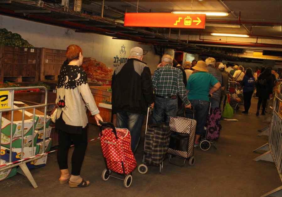 Needy people line up to fill up their baskets with foods and goods on Thursday ahead of the Passover