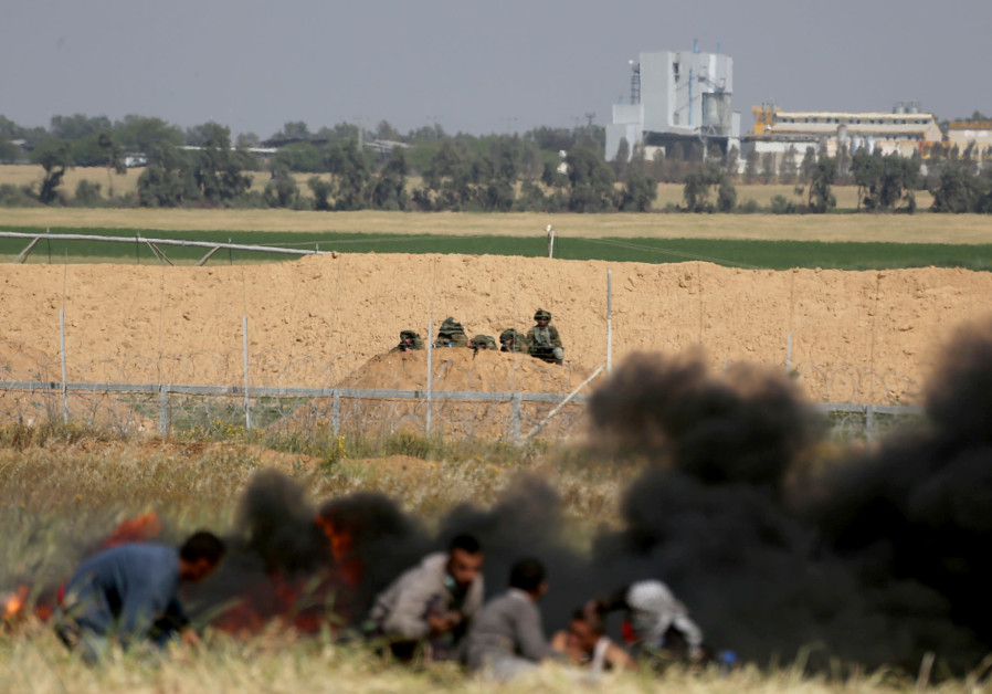 Palestinians take cover from Israeli snipers during clashes at the Gaza-Israel border at a protest i