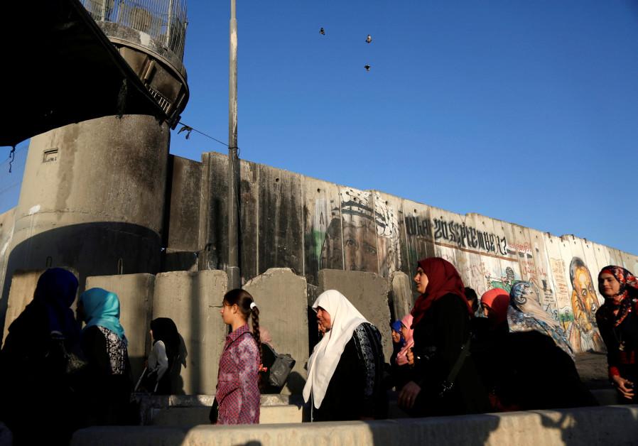 Palestinians wait to cross through Israeli Kalandiya checkpoint