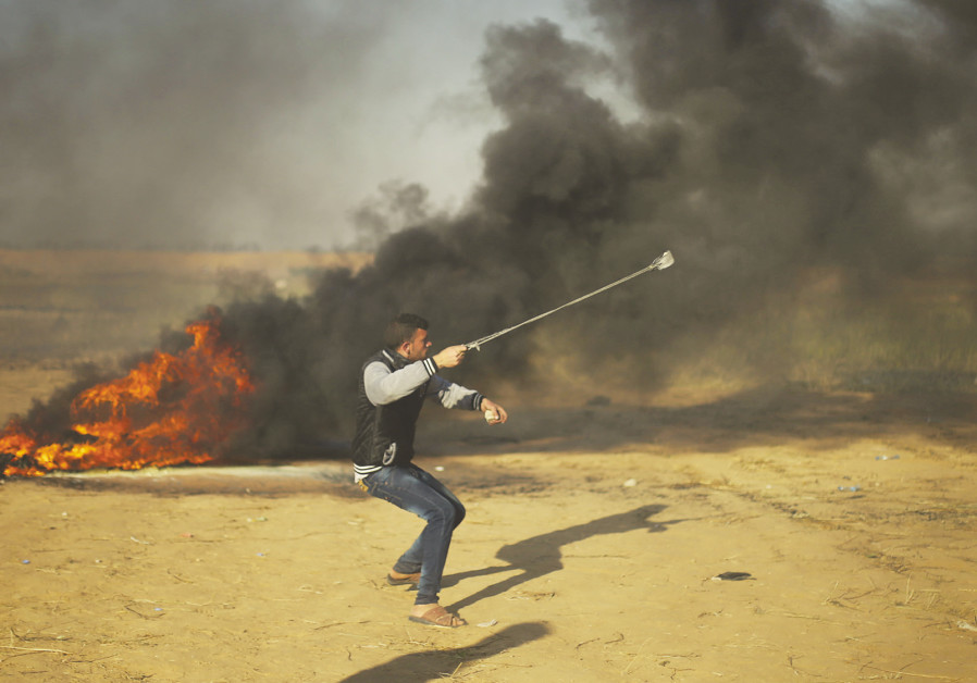 A Palestinian throws a rock towards Israeli forces on the Gaza border