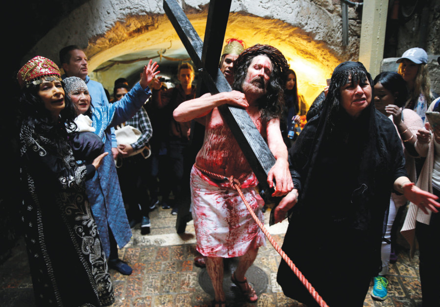 A worshiper reenacts Jesus's journey along the Via Dolorosa during a Good Friday procession in the Old City on March 30. (Reuters)