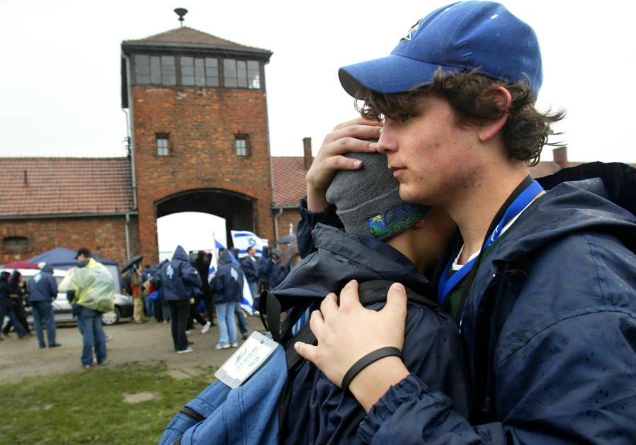 Two boys hug in front of the main railway building of the former Nazi death camp Birkenau (Auschwitz