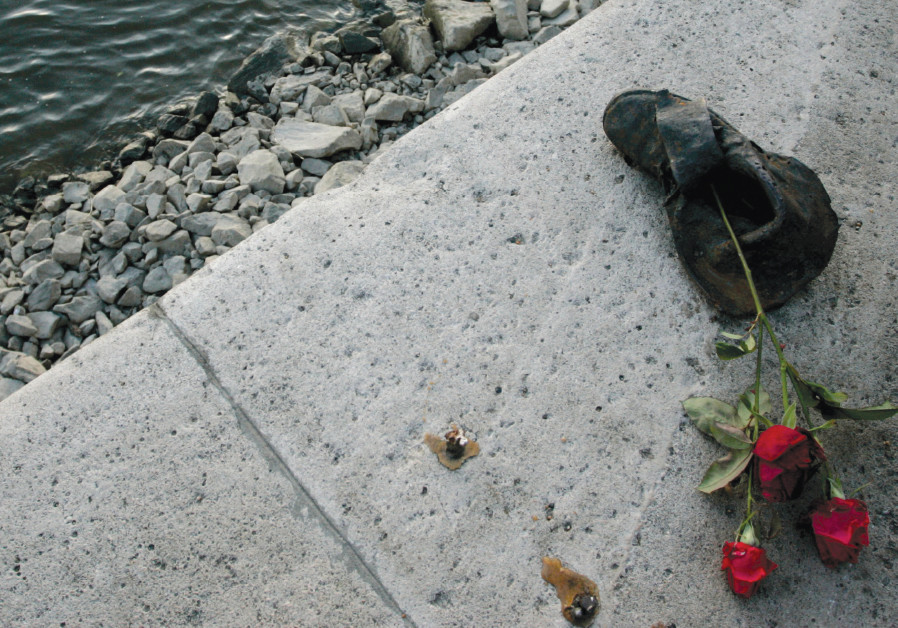 ROSES ARE placed on a bronze sculpture of a shoe on the banks of the River Danube in Budapest, part