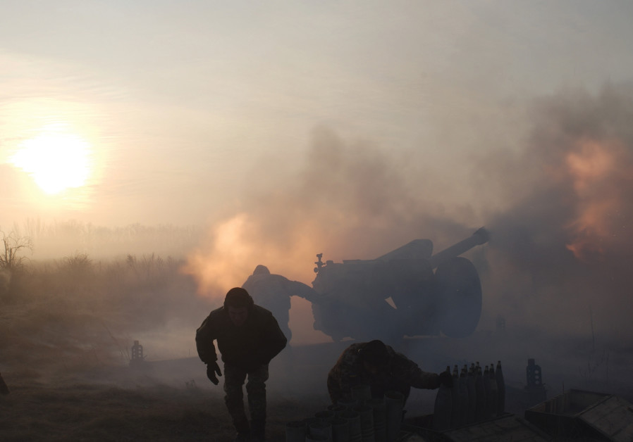 Ukrainian soldiers fire artillery during the conflict in Donbas