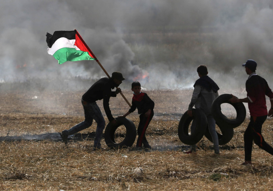 Palestinian protesters carry tires to burn them during clashes with Israeli troops at Israel-Gaza bo