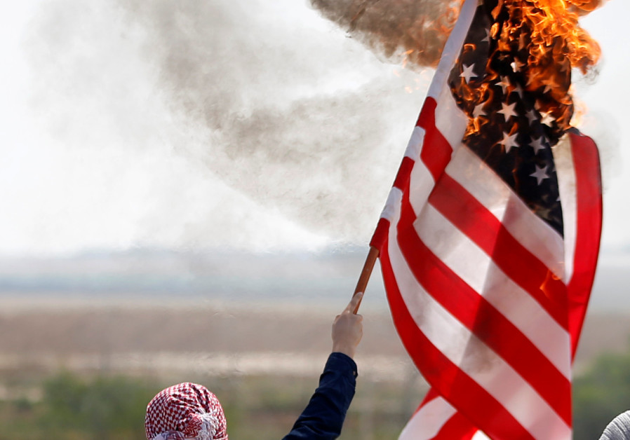 A Palestinian burns an American flag during protests in Gaza