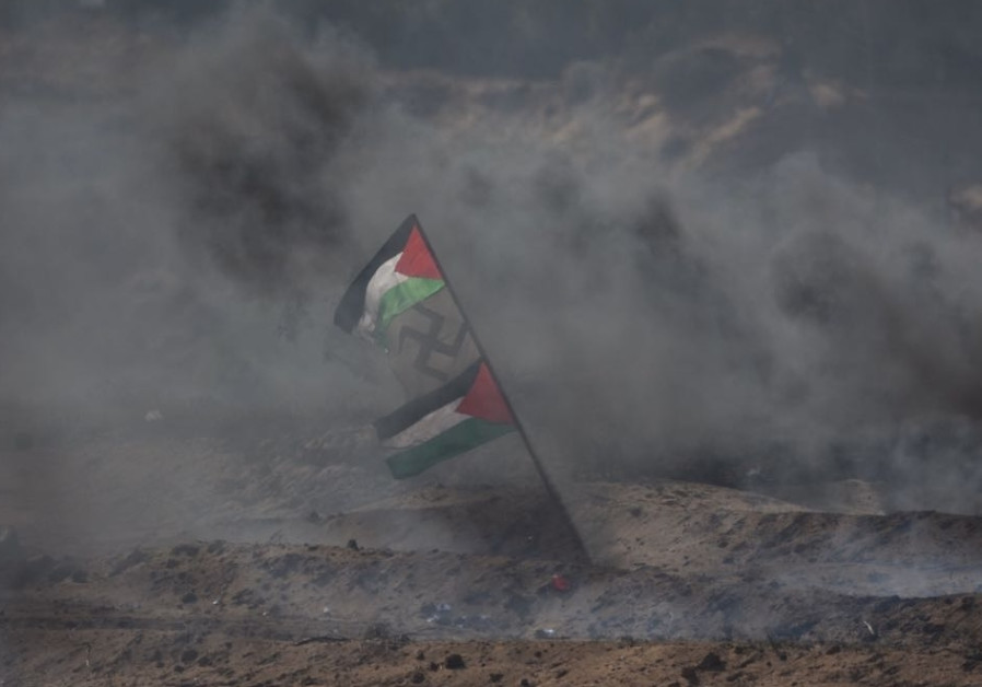 Palestinian flags flank a swastika in the midst of smoke during protests in Gaza