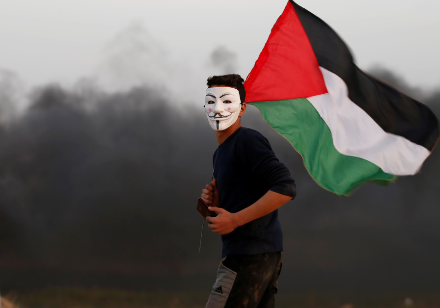 A Palestinian wears an 'Anonymous' mask and holds a Palestinian flag during protests in Gaza