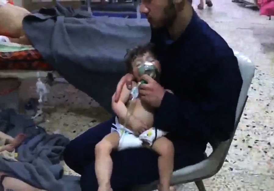 A volunteer holds an oxygen mask over a child's face at a hospital in Douma, Syria