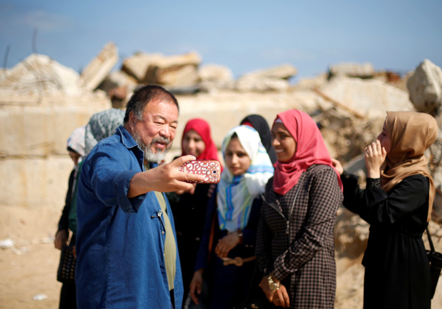Chinese artist Ai Weiwei takes a selfie with Palestinian girls as he works on a documentary film