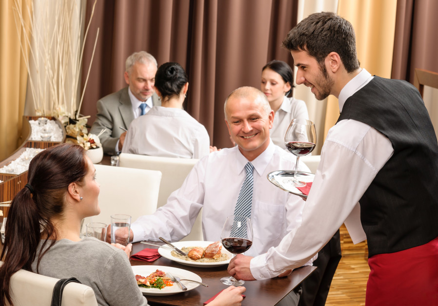 A waiter serves people at a restaurant