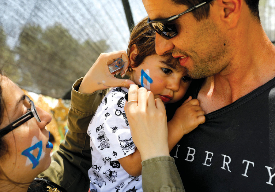 A SOLDIER paints a Star of David on a child's cheek during a display of IDF equipment and capabiliti