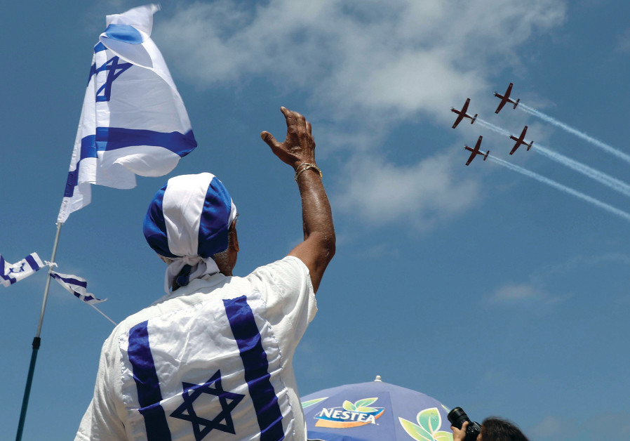 PEOPLE WATCH the Israel Air Force Aerobatic team fly over the Mediterranean Sea during Independence