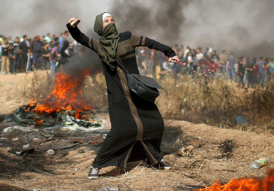 A girl hurls stones during clashes with Israeli troops at a protest at the Israel-Gaza border
