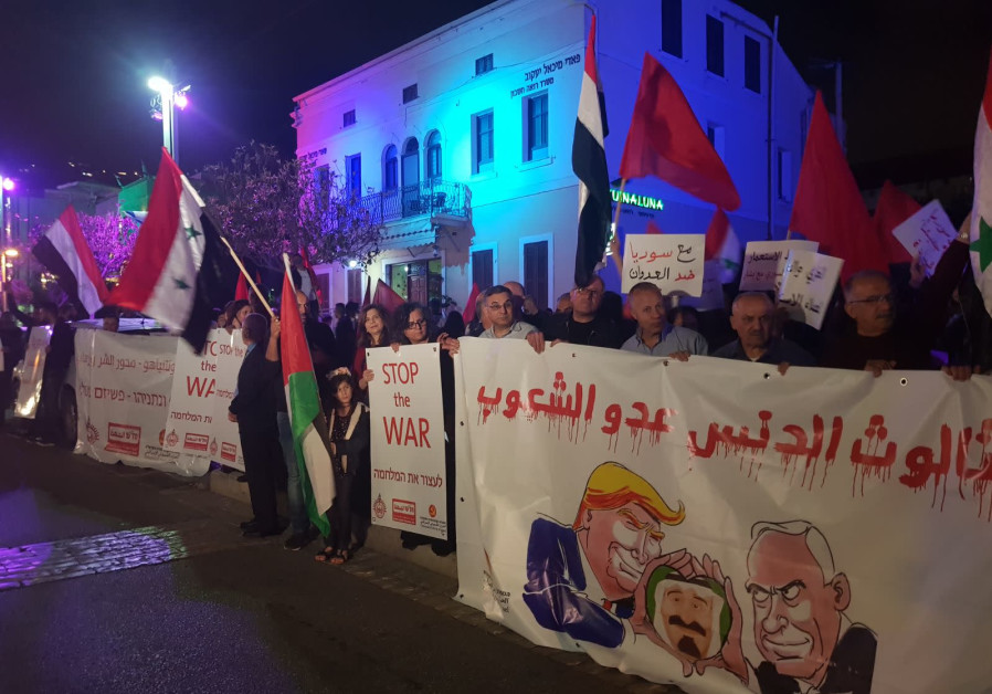 People protest the recent air strikes in Syria in front of the defunct US consulate in Haifa